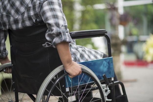 Mand i skjorte sidder i en kørestol