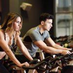En kvinde og en mand motionerer på nogle motionscykler